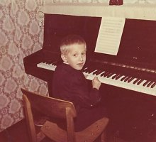 Nuotraukoje – žinomas muzikantas vaikystėje prie močiutės dovanoto pianino: atpažįstate jį?