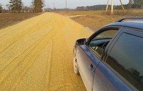 Aukso kelias: ūkininkas duobėtą vieškelį užlygino grūdais