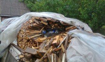 69-erių Vievio seniūnijos gyventoja naminę slėpė malkų kūgyje