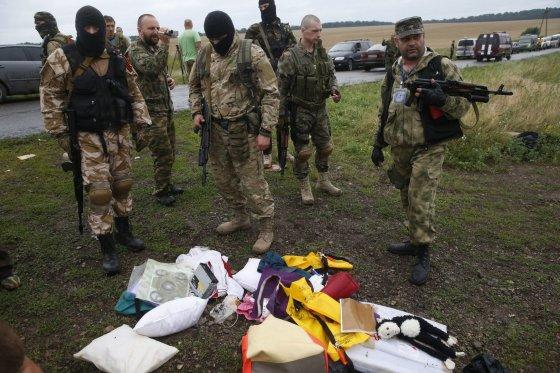 """AFP/""""Scanpix"""" nuotr./Ginkluoti teroristai trukdo tyrėjams dirbti katastrofos vietoje"""