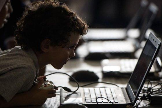 """AFP/""""Scanpix"""" nuotr./Vaikas žaidžia su kompiuteriu"""