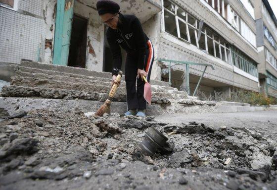 """""""Reuters""""/""""Scanpix"""" nuotr./Delbacevo mieste prie daugiabučio laiptinės nukrito artilerijos sviedinys."""
