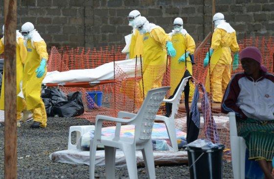 """AFP/""""Scanpix"""" nuotr./Nešamas nuo Ebolos viruso mirusio žmogaus kūnas"""