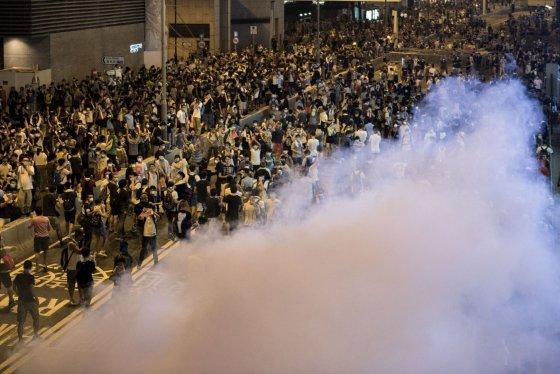 """AFP/""""Scanpix"""" nuotr./Honkonge protestuotojai buvo vaikomi panaudojus ašarines dujas."""