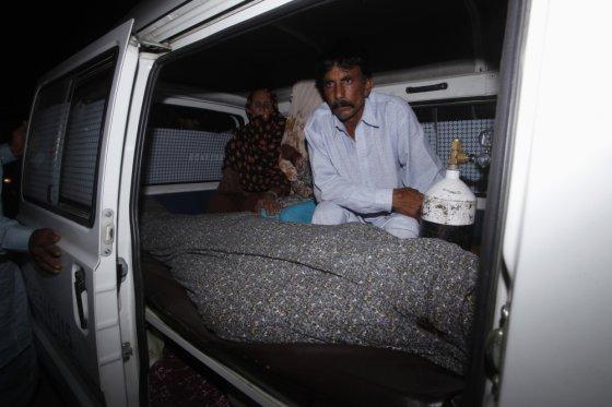 """""""Reuters""""/""""Scanpix"""" nuotr./Mohammadas Iqbalas prie savo žmonos palaikų"""