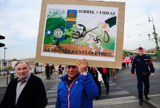 """""""Reuters""""/""""Scanpix"""" nuotr./Protestuotojas laiko plakatą, kuriame lygina valdančiąją Fisesz partiją su ultradešiniaisiais Jobbik"""
