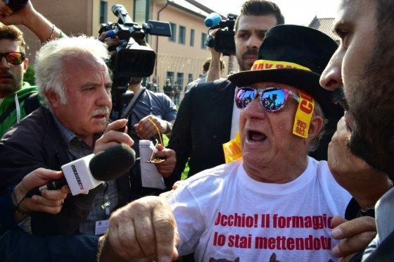 """AFP/""""Scanpix"""" nuotr./Protestuotojas prie ligoninės, kurioje visuomenei naudingą darbą atlieka buvęs Italijos premjeras Silvio Berlusconi"""