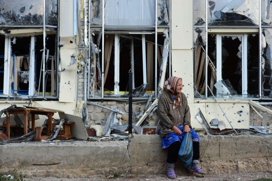 Pagyvenusi moteris šalia nuniokoto pastato
